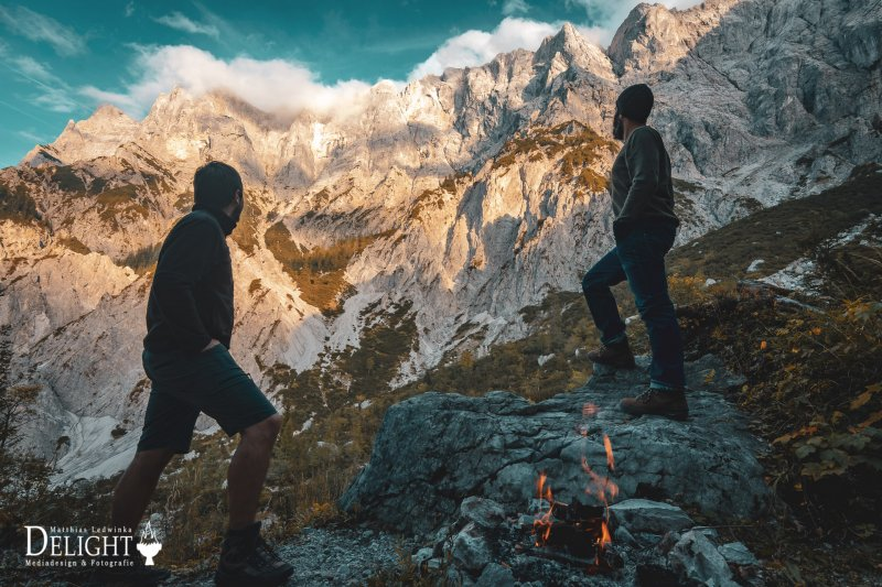 Two hikers in front of an impressive alpine mountain range at sunset.